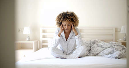pyjama: Depressed african-american young woman wearing in pyjama sitting on her bed at home