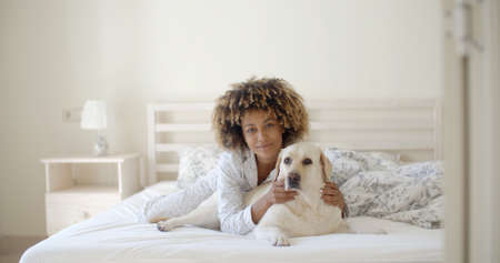 De jonge vrouw houdt een hond, terwijl tot op een bed in de woning