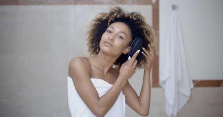 Beautiful black woman brushing hair in bathroom. Stock Photo