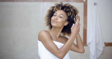 pulverizador: La mujer joven en una toalla usando spray para el cabello en el baño
