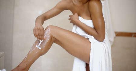 woman in bath: Young woman shaving legs with razor in bathroom