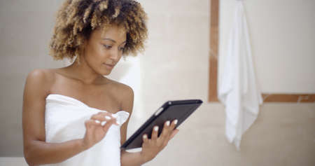 woman in bath: Young woman wearing bath towel and using tablet computer in the bath