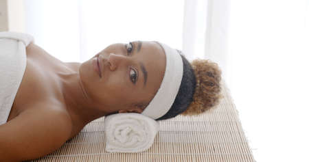 revitalize: Young beautiful and healthy african american woman in spa salon looking at the camera