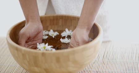 aroma bowl: Close up of a female hands with bowl of aroma spa water on table