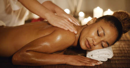 African-american woman having therapy massage of back in the spa salon slow motion