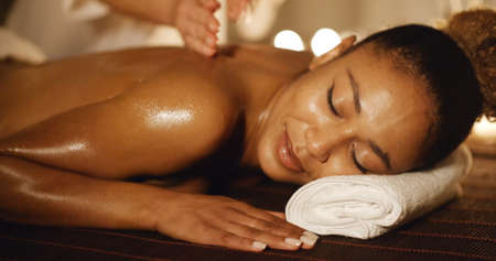 slow motion: African-american woman having therapy massage of back in the spa salon slow motion