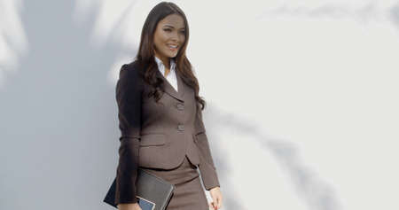 staying: Business woman in black suit staying in front of white wall and keep smiling
