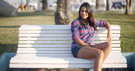 girl legs: Happy young woman relaxing and sitting on a bench in a park in summer