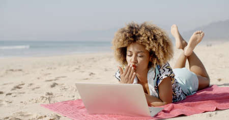 surfing the net: Young african american woman smiling while surfing the net at beach.