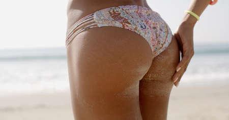 bikini bottom: Back view of a sandy woman buttocks on the beach in