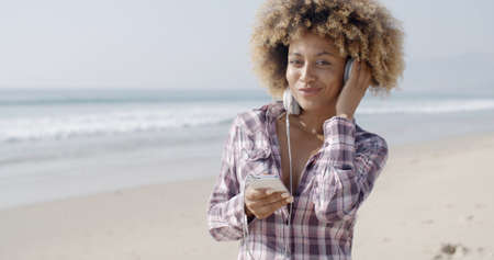 relaxing beach: Portrait of a young african american girl listening to music with headphones