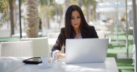 business woman working: Attractive young businesswoman working on her laptop computer at a table under a tree at an open-air restaurant