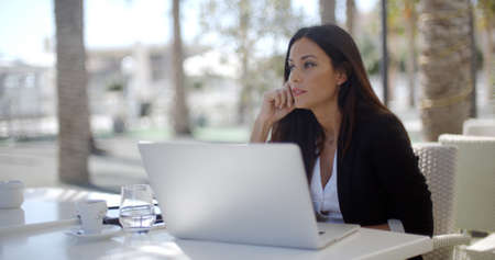 business woman working: Businesswoman sitting thinking at a restaurant table leaning her chin on her hand as she stares into the distance with an open laptop in front of her. Stock Photo
