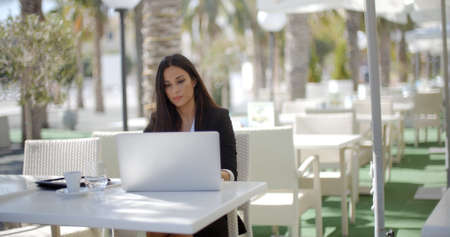 laptop outside: Businesswoman sitting thinking at a restaurant table leaning her chin on her hand as she stares into the distance with an open laptop in front of her. Stock Photo