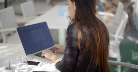 business woman working: Businesswoman sitting at a restaurant table typing on her laptop computer as she enjoys a cup of coffee  over the shoulder view of the computer