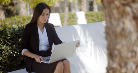 business woman working: Stylish attractive young businesswoman sitting outdoors in the shade of a tree working on a laptop computer in the park