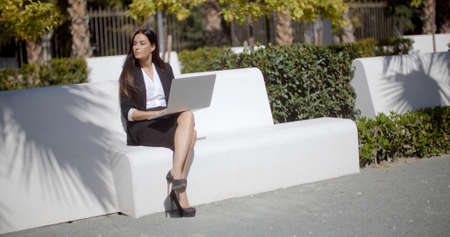 business woman working: Young businesswoman using a laptop on a white park bench as she sits in the sunshine looking expectantly to the left of the frame as she waits for someone.
