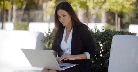 persona sentada: Estilo joven y atractiva mujer de negocios sentado al aire libre en la sombra de un árbol de trabajo en un ordenador portátil en el parque Foto de archivo