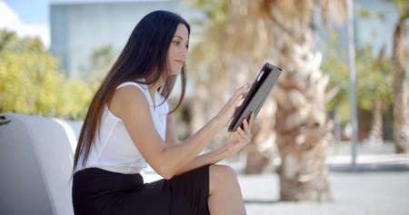 gente sentada: mujer joven que usa su tablilla sonríe al aire libre un ella se sienta en un banco en el parque disfrutando de la vista lateral cálido día de verano Foto de archivo