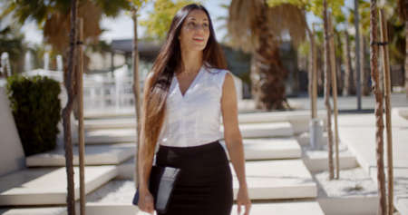 pencil skirt: Young businesswoman walking through an urban park carrying her laptop under her arm and looking aside as something catches her interest