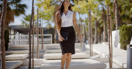 pencil skirt: Confident stylish young woman walking through an urban park looking to the side as she strolls along