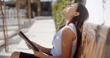 tilted view: Young businesswoman relaxing on an outdoor wooden bench sitting with her head tilted back and eyes closed while holding a tablet computer  side view