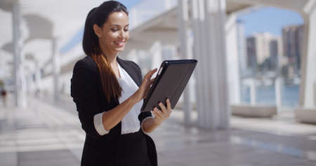 woman business suit: Smiling attractive young professional woman standing in a high key urban environment surfing the internet on a tablet computer Stock Photo