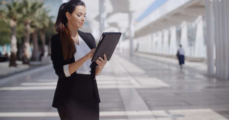 women business: Elegant businesswoman standing on a seafront promenade holding a tablet computer in her hands looking at the camera