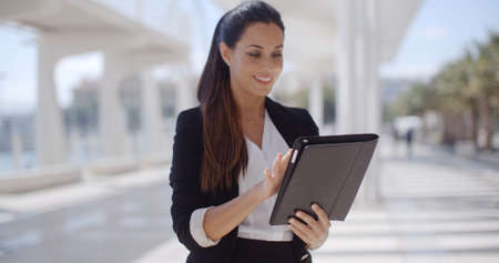 woman business suit: Elegant businesswoman standing on a seafront promenade holding a tablet computer in her hands looking at the camera