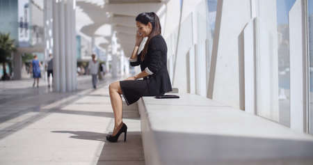 business woman phone: Elegant businesswoman talking on her mobile phone as she sits on a white bench in an urban street   low angle profile view