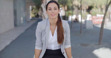 brunette: Estilo sonriente mujer de negocios joven confía en un pueblo o entorno urbano que se inclina hacia la cámara con una sonrisa