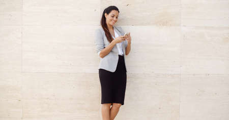 cream colored: Pretty young woman standing leaning against a neutral cream colored wall with copyspace on either side checking her mobile phone for messages