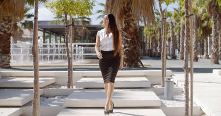 pencil skirt: Elegant young businesswoman walking through a park looking off to her right as something catches her interest  full length approaching the camera