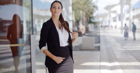 commercial building: Elegant young businesswoman standing waiting outside a commercial building overlooking a waterfront promenade with a pensive expectant expression as she watches for someone