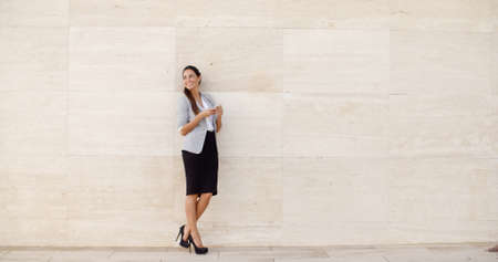 bilateral: Stylish businesswoman standing against a neutral cream colored wall holding her mobile phone and looking back over her shoulder  full length with bilateral copyspace
