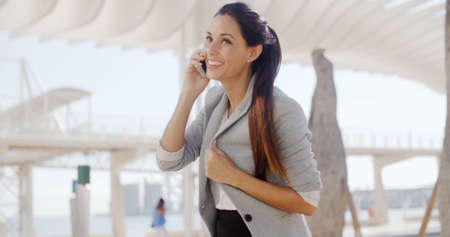 successful woman: Attractive stylish young woman talking on her mobile phone in a high key white urban environment  upper body side view