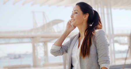 Attractive stylish young woman talking on her mobile phone in a high key white urban environment  upper body side view