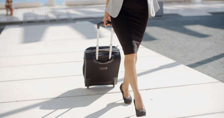 suitcases: Elegant woman in stylish high heels and dress going on a business trip pulling her suitcase along the sidewalk behind her  close up of her legs. Stock Photo