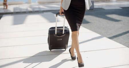 maletas de viaje: Mujer elegante en zapatos de tacón alto elegantes y el vestido va en un viaje de negocios tirando de su maleta a lo largo de la acera detrás de ella de cerca de sus piernas. Foto de archivo