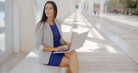 browses: Elegant businesswoman relaxing on a bench on a waterfront promenade and working on a laptop computer reading information on the screen as she browses the internet. Stock Photo