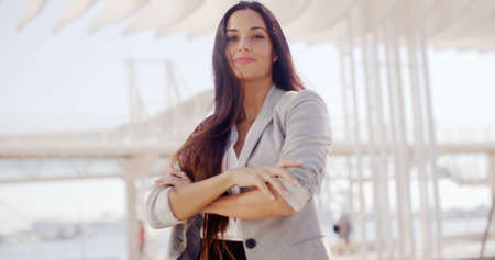 bilateral: Confident attractive woman with long brown hair standing in the center of the frame with folded arms smiling at the camera  high key bilateral copyspace Stock Photo