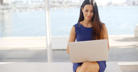 business woman working: Attractive young woman sitting on a waterfront bench using a laptop computer sitting smiling at the camera with a thoughtful expression  with copyspace Stock Photo
