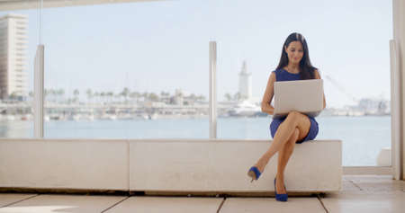 Attractive young woman sitting on a waterfront bench using a laptop computer sitting smiling at the camera with a thoughtful expression  with copyspace Foto de archivo