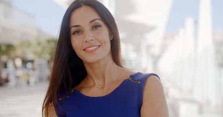 femme brune: Tête et des épaules Portrait d'une jeune femme brune assez sympa debout en plein air dans un environnement urbain blanc high key souriant à la caméra