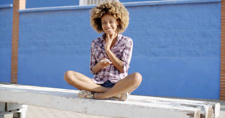 slow motion: Young female using mobile phone while sitting on a road slow motion