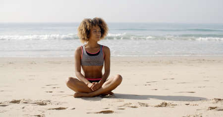 position: Slim girl on a beach in lotus position in bikini