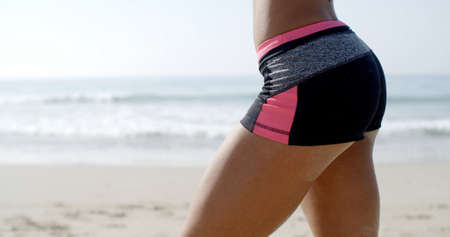 Bottom of a lady in fitness wear against beach background Stock Photo
