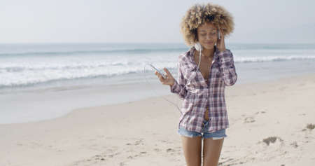 slow motion: Young woman listening to music and dancing at the beach slow motion