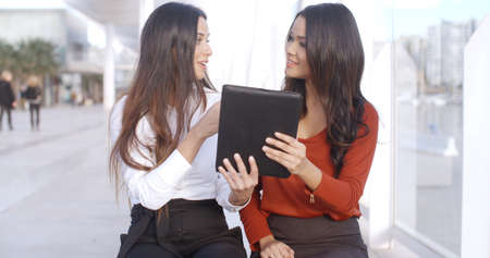 formal wear clothing: Two women sitting outdoors on a high key urban esplanade discussing information on a tablet computer which they are both holding