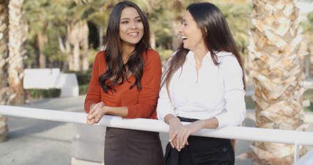 mujeres juntas: Dos atractivas mujeres jóvenes en el chat en un parque tropical de pie urbana apoyándose en un riel riendo y bromeando juntos